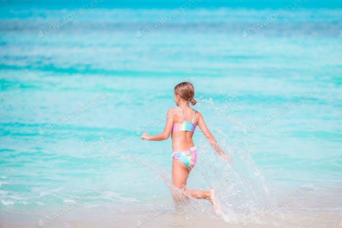 Kleines glückliches Mädchen spritzt. Kid läuft zum türkisfarbenen Wasser bereit zu schwimmen