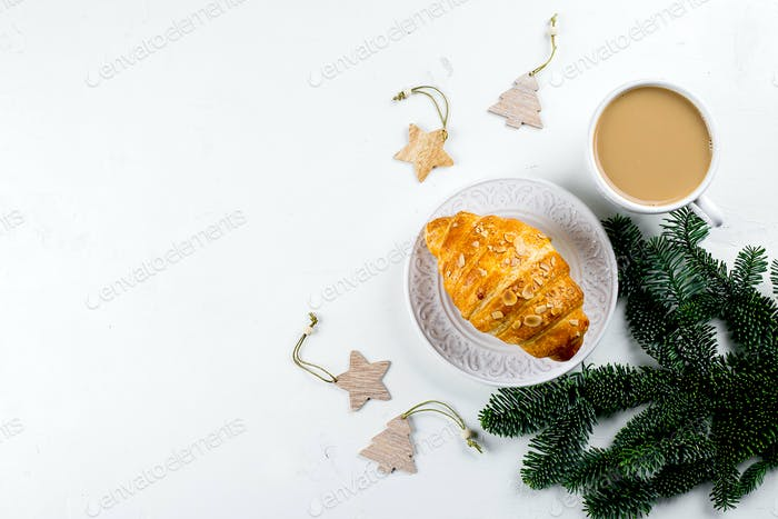 Christmas breakfast. Cup of coffee, croissant and holiday decoration toys
