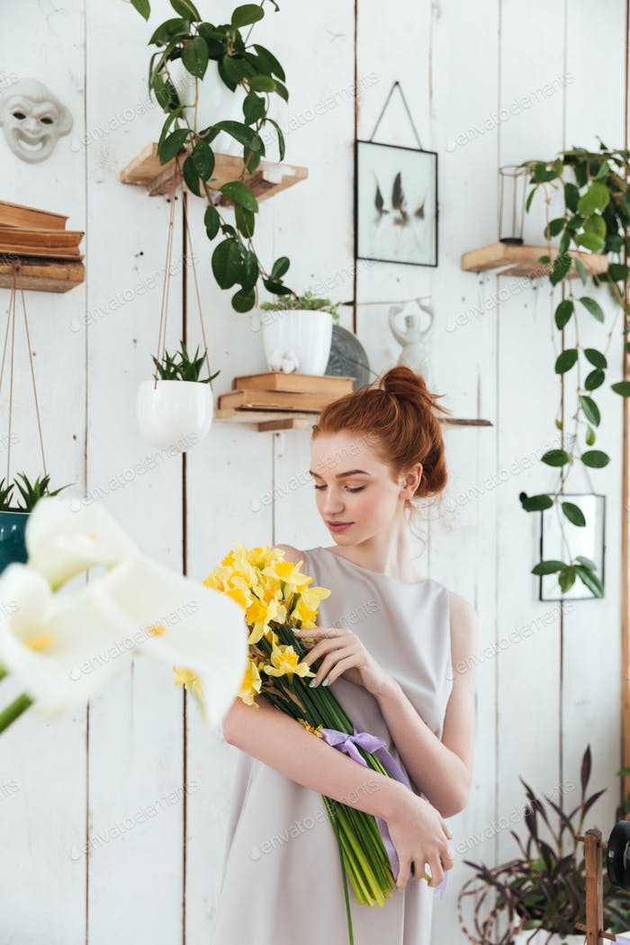 Young woman hugging bouquet of yellow flowers in workshop