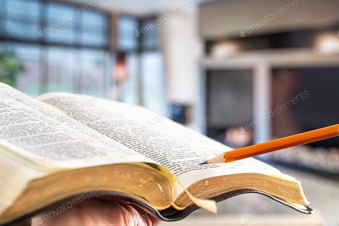 Bible with a pencil, against the background of the living room.