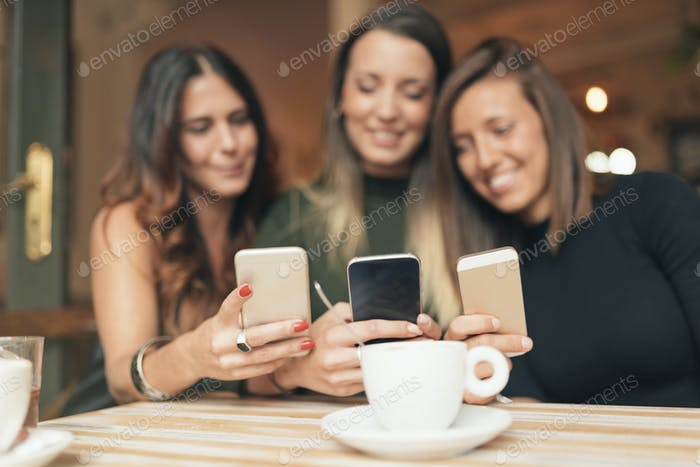 Friends watching social media in a smart phone.