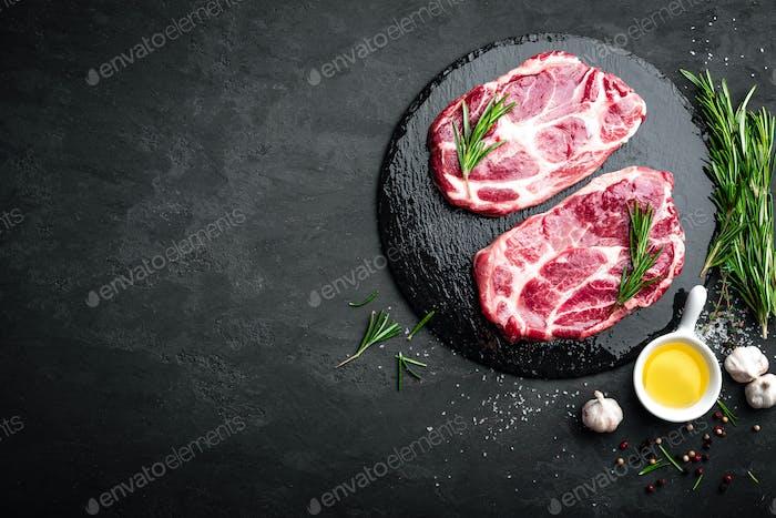 Kochen auf Küchentisch frisches rohes Schweinefleisch marmorierte Steaks auf schwarzem Hintergrund, Draufsicht