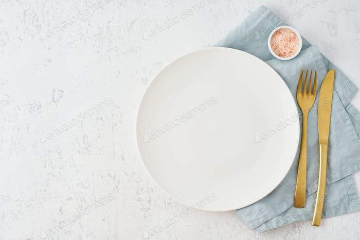 Leere weiße Platte, Gabel und Messer auf weißem Steintisch, Kopierraum, mock up