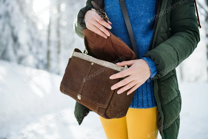 Midsection of woman with handbag standing outdoors in snowy winter forest.