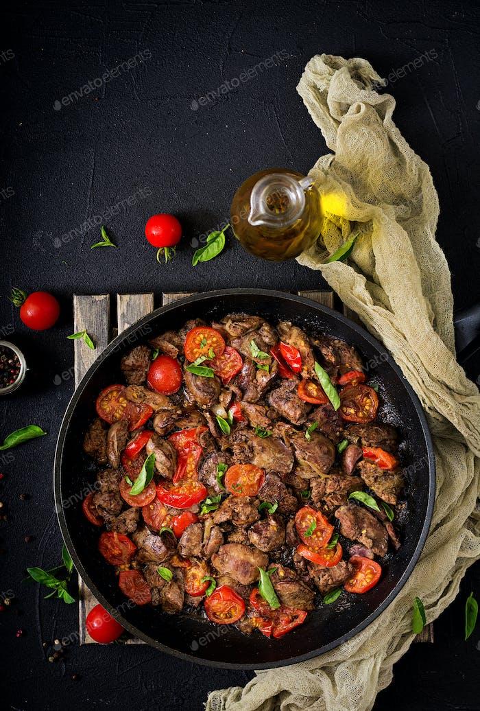 Hühnerleber (Innereien) mit Zwiebeln und Tomaten in einer Pfanne auf Armenisch. Flache Lag. Ansicht von oben