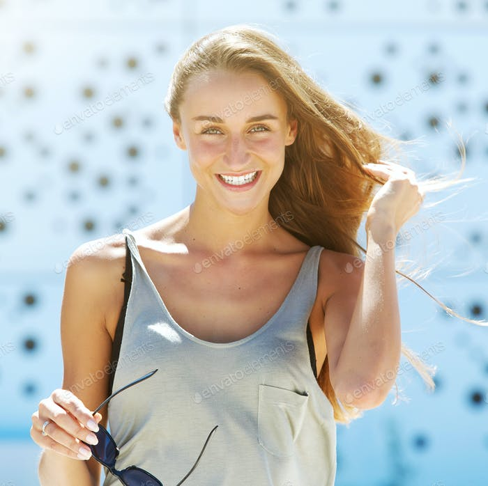 Cheerful young woman smiling outside