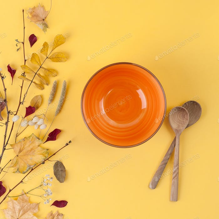 Bright orange empty bowl, wooden spoon and autumn leaves on a ye