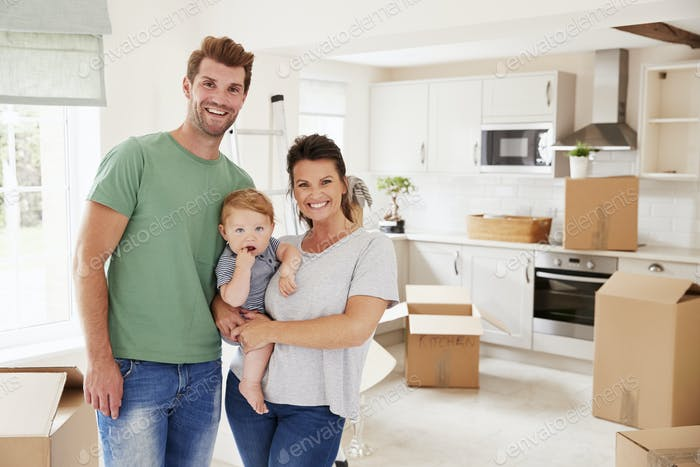 Portrait Of Family With Baby On Moving In Day