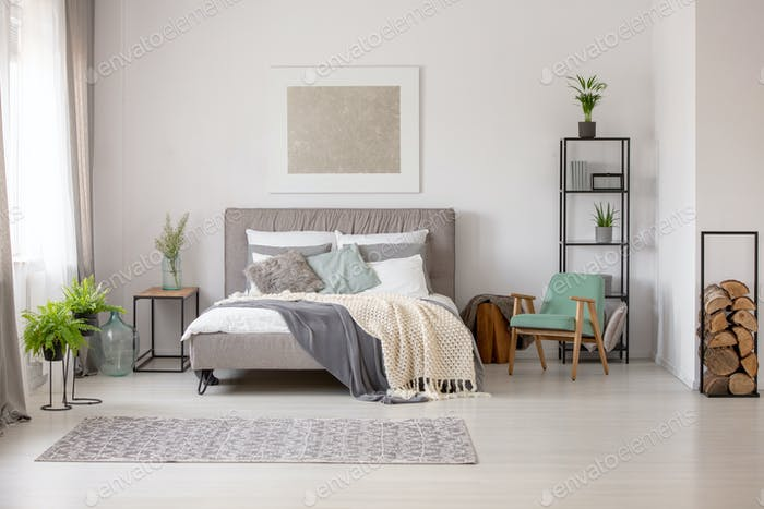 Knitted blanket on grey bed in bright bedroom interior with gree