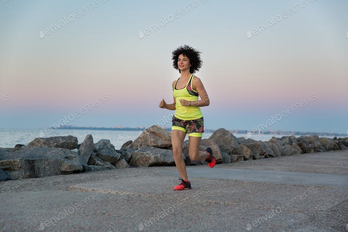 Young healthy woman jogging along the beach