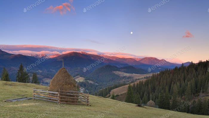 Panorama of sunrise in the mountains with a haystack