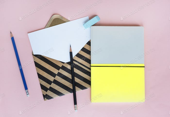 Stripe Envelope with Paper and Notebook on Pink Background