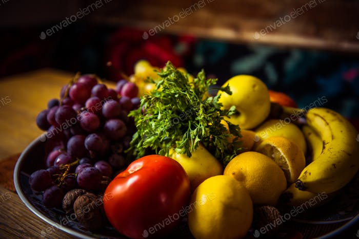 Mix of delicious fruits in a plate on a wooden table