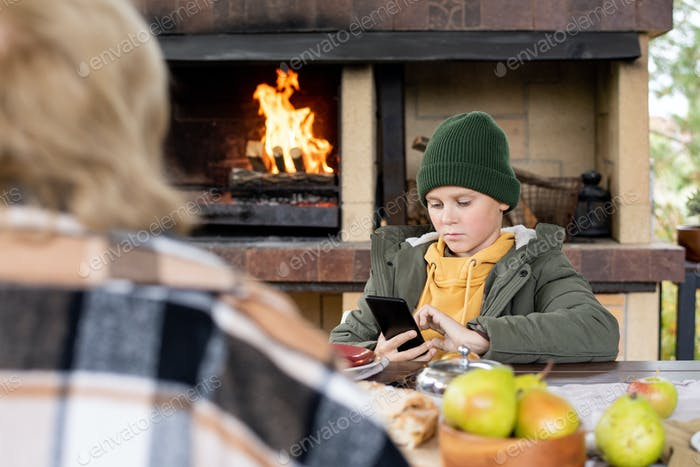 Serious clever schoolboy in beanie and warm jacket scrolling in smartphone