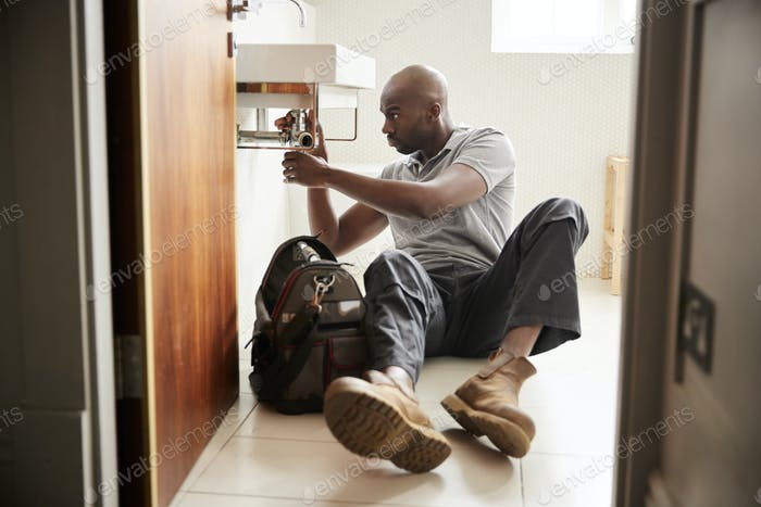 Young black male plumber sitting on the floor fixing a bathroom sink, seen from doorway, full length