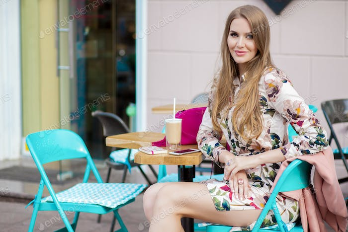 cool young hipster stylish woman sitting in cafe spring summer fashion trend, drinking coffee