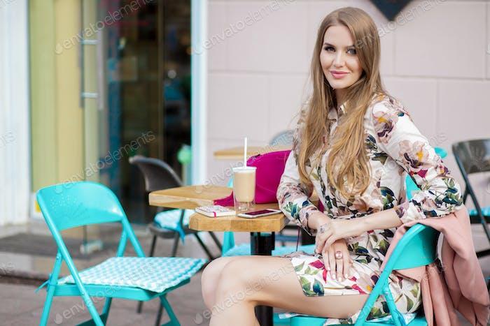 coole junge Hipster stilvolle Frau sitzt im Café Frühling Sommer Modetrend, Kaffee trinken