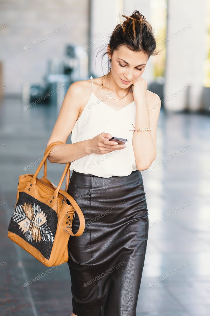 Refined smiling woman walking and writing or reading SMS messages online on a smart phone outdors