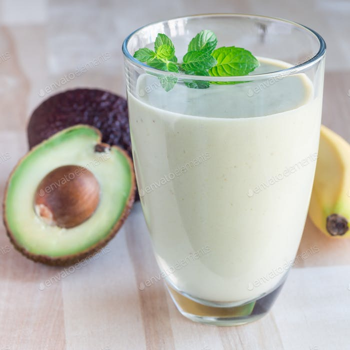 Smoothie with avocado, banana, milk and honey on wooden backgrou