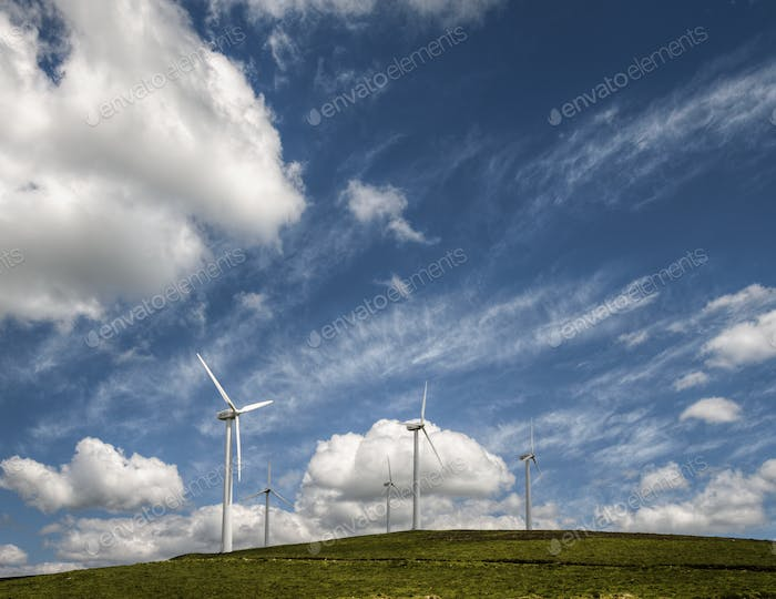 Wind farm on a green hill under a blue sky