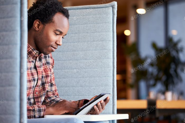 Geschäftsmann am Schreibtisch In Kabine In Moderne Büro-Arbeitsplatz Mit Digital Tablet
