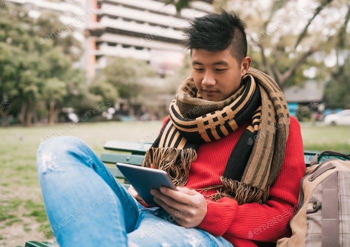 Asiatischer Mann mit seinem digitalen Tablet.