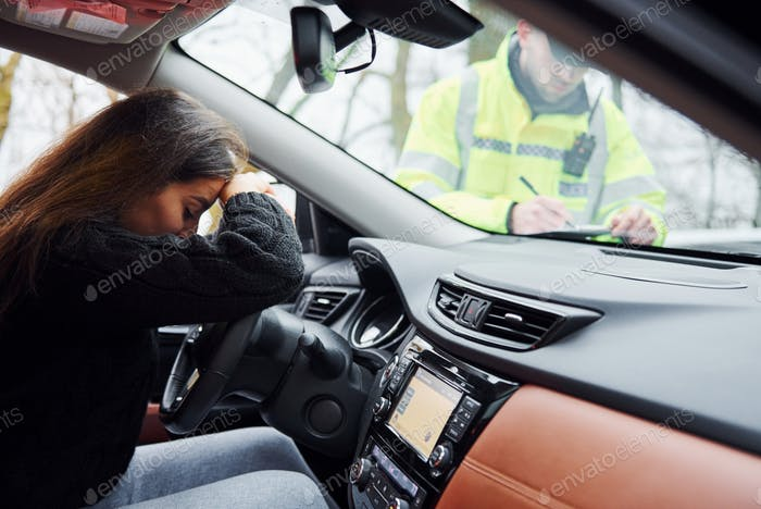 Girls feels bad. Male police officer in green uniform checking vehicle on the road