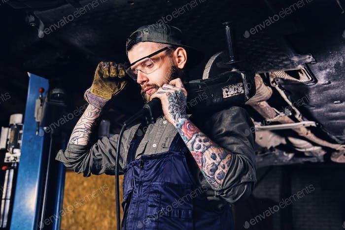 Mechanic holds angle grinder on a shoulder.