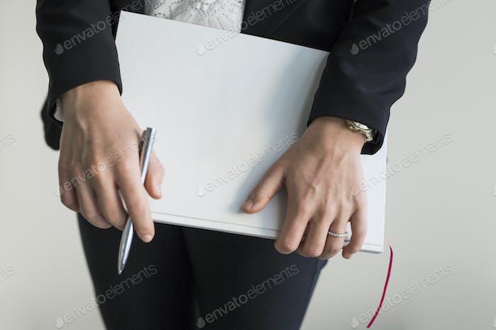Sección media de la mujer que sostiene el archivo mientras está de pie en la oficina