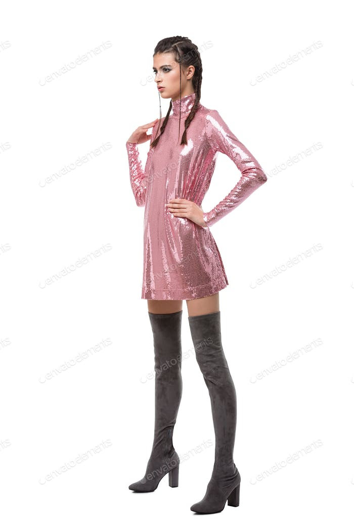 Young lady looking aside while standing in pink dress in sequins and knee high boots
