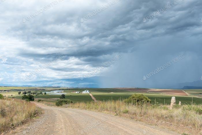 Gravel road, Bloukruin Manitoba farm and thunderstorm near Fouriesburg