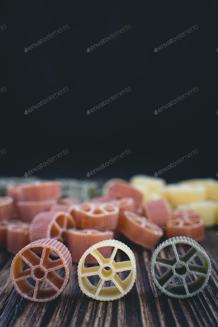 Colorful wheel pasta detail on a wooden background