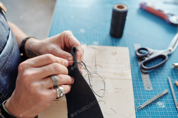 Hands of leatherworker with piece of black leather sewing new item