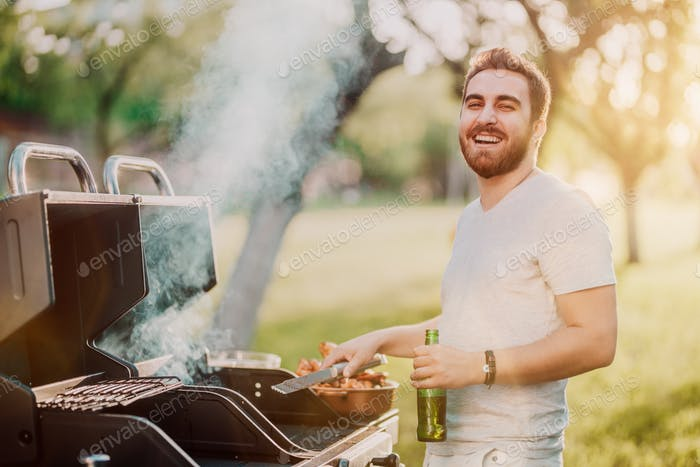 Portrait of laughing handsome guy having a great time at barbecue grill party