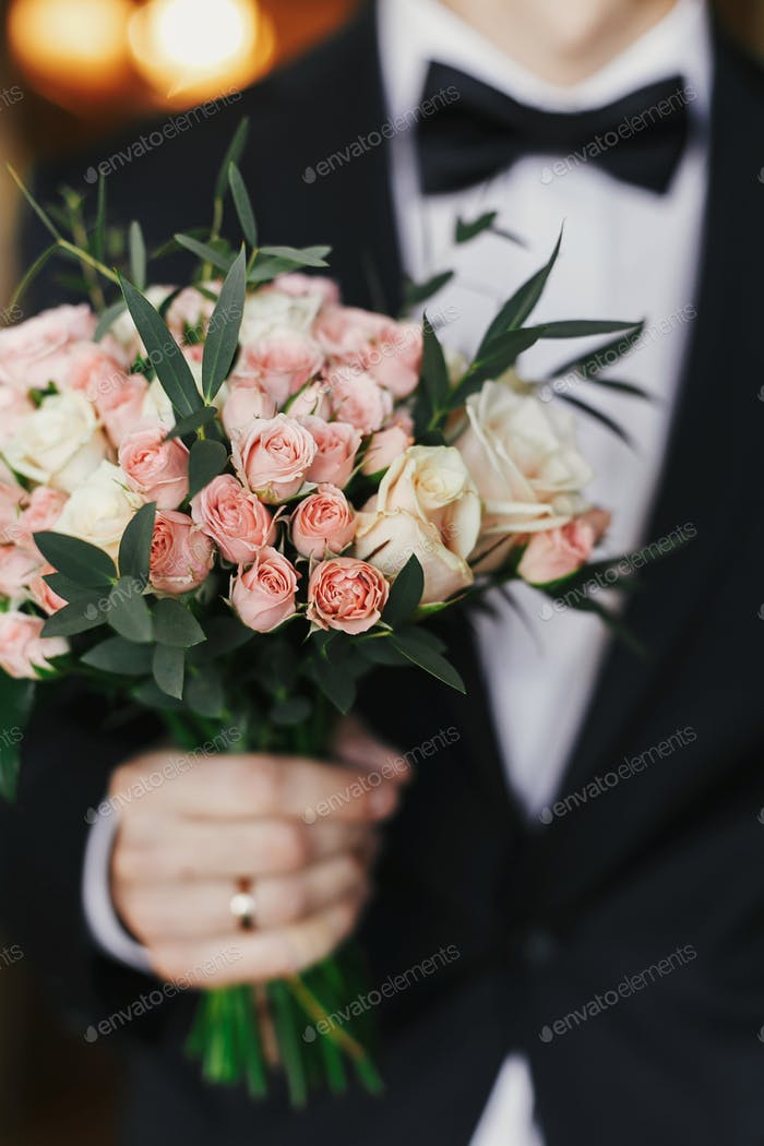 Groom holding stylish bouquet with roses and eucalyptus