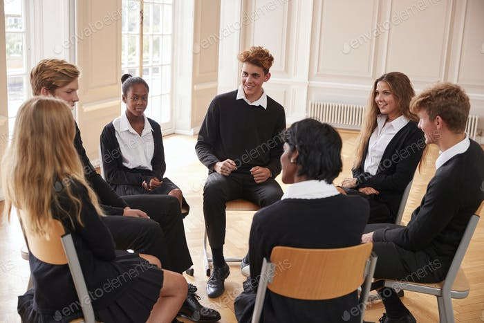 Group Of Teenage Students Having Discussion In Class Together