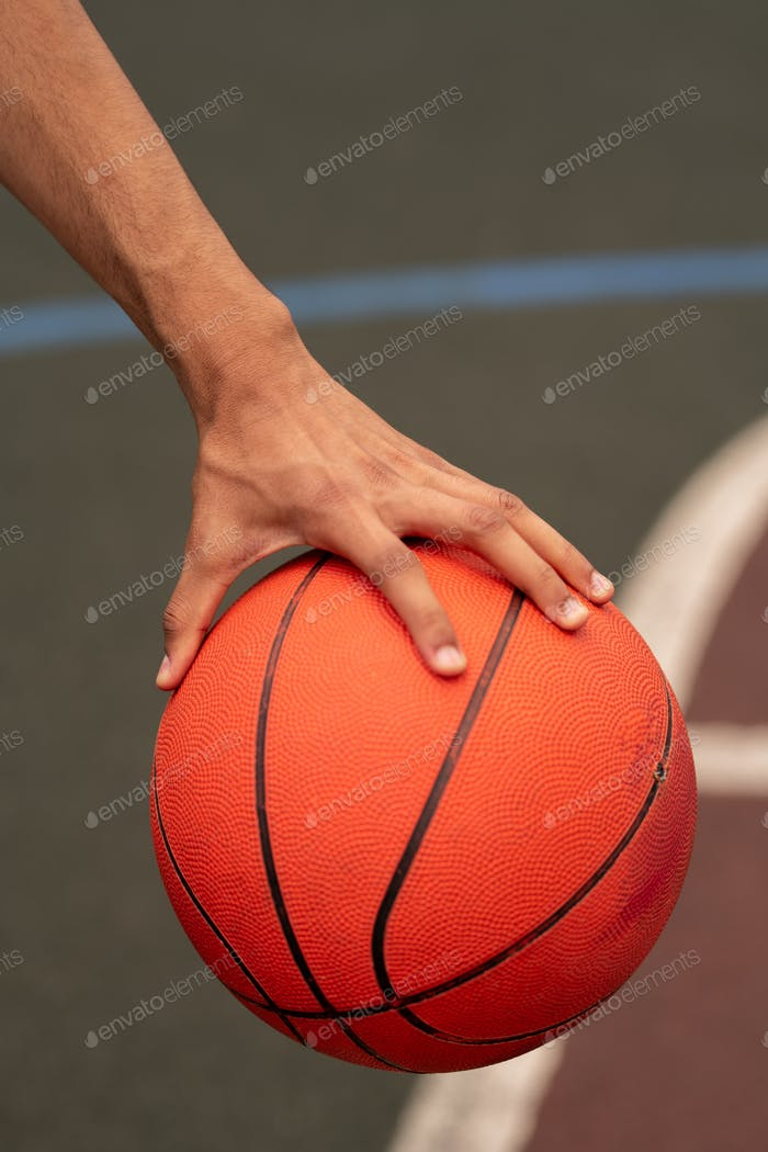 Hand of young active basketballer holding ball while getting ready to throw it