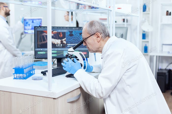 Senior scientist preparing and analyzing microscope slides