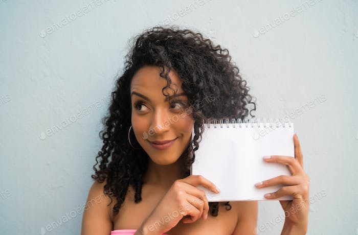 Young afro woman holding blank paper.