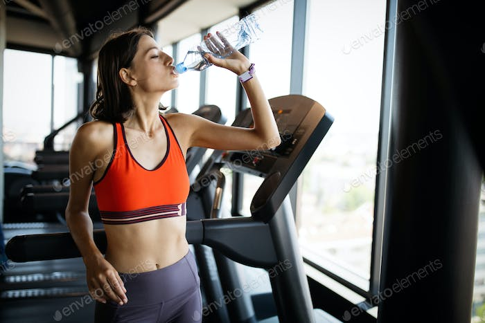 Refreshing after workout. Beautiful young woman drinking water to stay hydrate