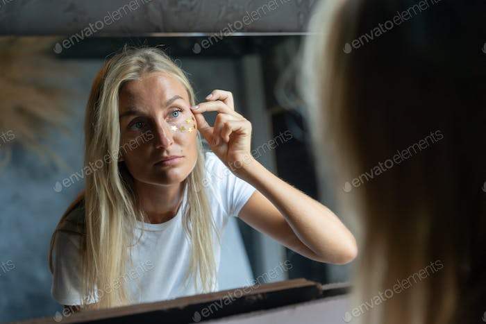 A woman looks in the mirror and glues glitter stars on her face.