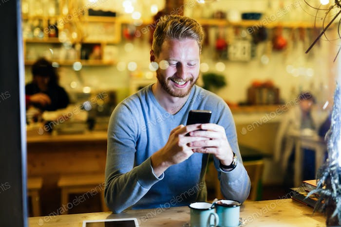 Handsome man using mobile phone in coffee shop