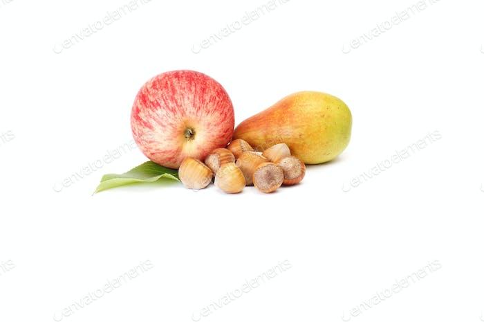 Reife Nüsse, Birne und Apfel auf einem weißen.