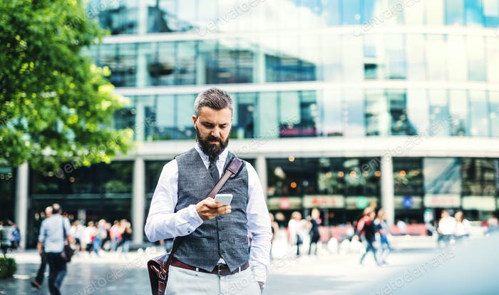 Hipster businessman with smartphone standing on the street in city.
