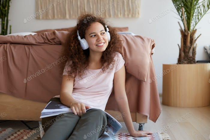 Portrait of cheerful young curly mulatto lady sitting in room, enjoying his favorite song