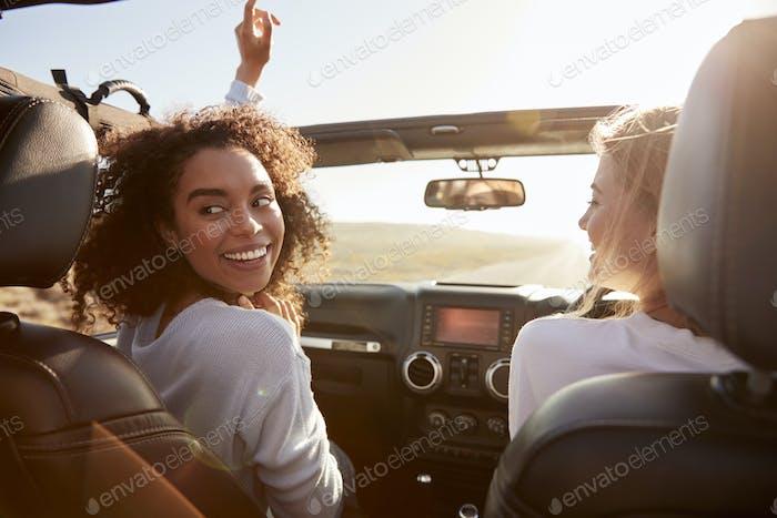 Zwei Freundinnen fahren mit Schiebedach offen, eine dreht sich um