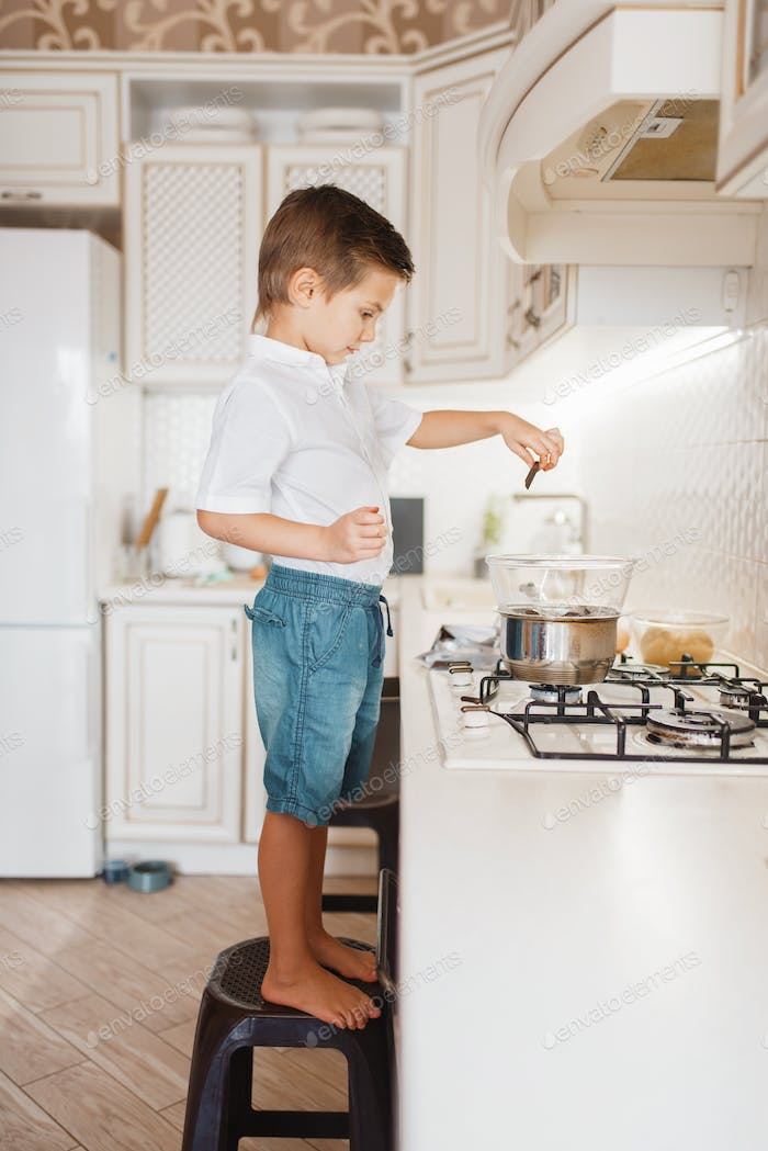 Litte boy cooking melt chocolate on the kitchen