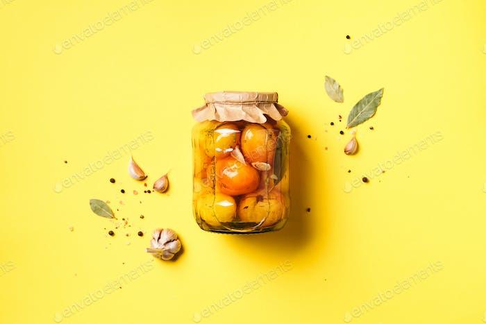Eingelegte Tomaten in Glas auf gelbem Hintergrund. Draufsicht. Flache Lag. Kopierraum. Konserven und konserviert
