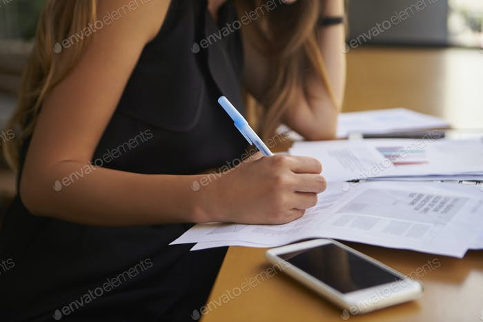 Businesswoman writing in an office, mid section, side view