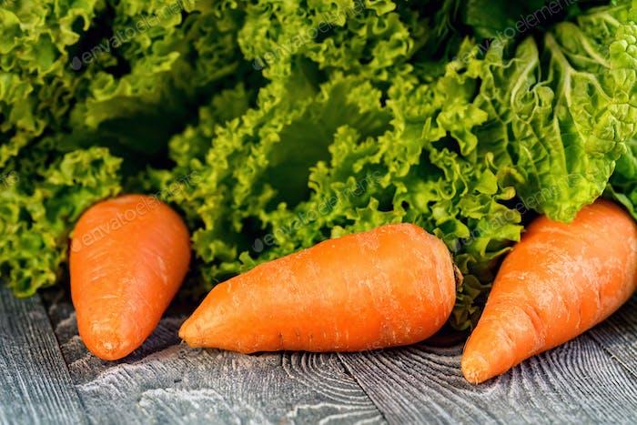 Rohe Karotte mit verschiedenen Grüns mit Copyspace